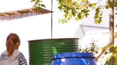 Two girls playing in the garden of large barrels of water Stock Footage