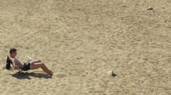A young boy reads lying on the beach - stock footage
