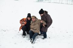 senior snow accident and people helping - stock photo