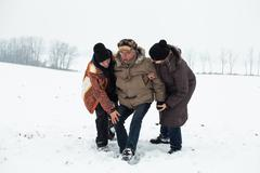 senior snow accident and people helping him - stock photo