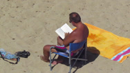 Stock Video Footage of A man is reading a book sitting on the beach