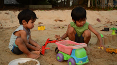 Two Cute Asian Boys Playing With Toys At The Beach Stock Footage