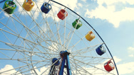 Stock Video Footage of Underside view of a ferris wheel over blue sky