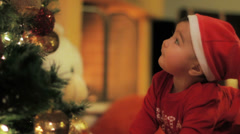 A little baby Santa Claus at a lighted Christmas tree 2 Stock Footage