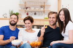 Laughing group of friends watching television Stock Photos