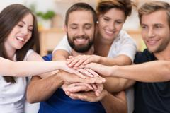 Friends stacking hands Stock Photos
