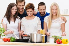 group of beautiful young women cooking - stock photo