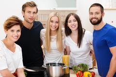 Group of happy young friends preparing lunch Stock Photos