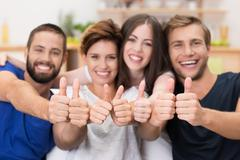 young men and women giving a thumbs up - stock photo