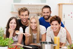 Smiling multicultural group of friends cooking Stock Photos