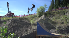 Sports & fitness, mountain bike jump, with small twist through frame wide shot Stock Footage