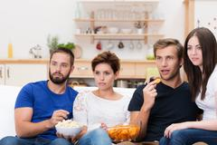 Group of friends watching a gripping movie Stock Photos