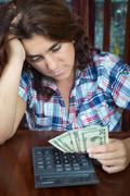 Hispanic woman counting money at home to pay the bills Stock Photos