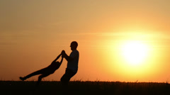 Dad turns in a circle of his son at sunset on nature Stock Footage