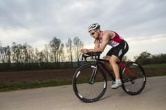 germany, triathlete riding bicycle - stock photo