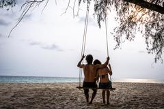 happy couple on a swing looking at the ocean. koh kood island, south east asi - stock photo