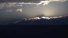 Time-lapse, setting sun behind clouds long shot Stock Footage