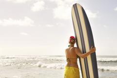 Usa, hawaii, mild adult woman standing with surfboard  on beach Stock Photos