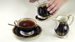 Hand adding brown sugar to cup of tea Stock Footage