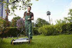 Germany, cologne, young man mowing lawn with push mower Stock Photos