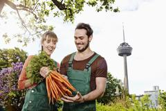 Germany, cologne, young couple holding bunch of carrots, smiling Stock Photos