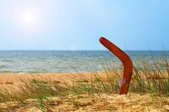 Landscape with boomerang on overgrown sandy beach. Stock Photos