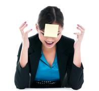 Businesswoman yelling with paper on forehead - stock photo