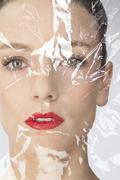 portrait of young woman wrapped in plastic foil, close up - stock photo
