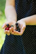Germany, baden wuerttemberg, girl holding black and red currant Stock Photos