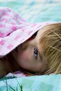 Germany, baden wuerttemberg, girl hiding under towel, close up Stock Photos