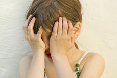 germany, baden wuerttemberg, girl hiding her face, close up - stock photo
