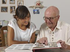 Germany, baden wuerttemberg, grandfather and granddaughter looking photo ablu Stock Photos