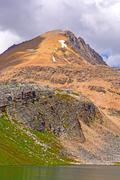 barren peak above an alpine lake - stock photo