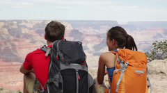 Couple hiking in Grand Canyon relaxing sitting - stock footage