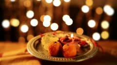 Locked-on shot of a spinning puja thali with rakhi, sweets and oil lamp Stock Footage
