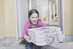 Germany, north rhine westphalia, cologne, girl taking pizza boxes from delive Stock Photos