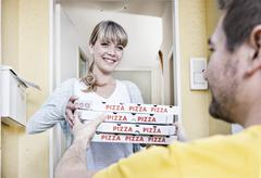 Germany, north rhine westphalia, cologne, young woman taking pizza boxes from Stock Photos