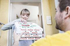 germany, north rhine westphalia, cologne, young woman taking pizza boxes from - stock photo