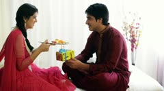 Teenage girl holding a puja thali and her brother sitting with a present Stock Footage