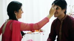 Pan shot of a teenage girl applying tilak to her brother at Raksha Bhandan Stock Footage