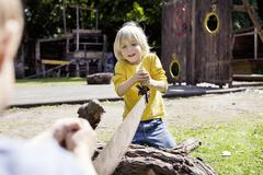 Stock Photo of germany, north rhine westphalia, cologne, boys playing in playground, smiling