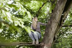 germany, north rhine westphalia, cologne, young woman sitting on wood - stock photo