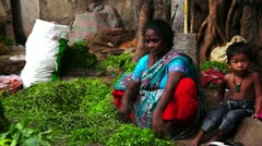 Locked-on shot of woman cleaning cilantro at a market stall - stock footage