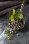Brass spoon with allspice corns and leaves on textile, close up Stock Photos