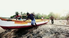 Pan shot of men pushing a boat in the sea - stock footage