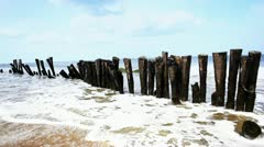 Locked-on shot of wooden posts on the beach Stock Footage