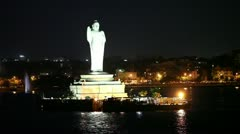 Pan shot of a statue of Lord Buddha lit up at night Stock Footage
