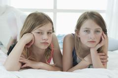 Germany, bavaria, sad girls lying on bed Stock Photos