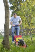 Germany, kaufbeuren, mid adult man gardening with lawn mower Stock Photos
