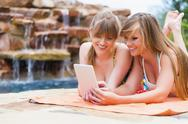 Young women using digital tablet at swimming pool, smiling Stock Photos